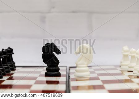 Black And White Chess Knights Opposite Each Other On A Chessboard. Concept Of Chess Strategy, Opposi