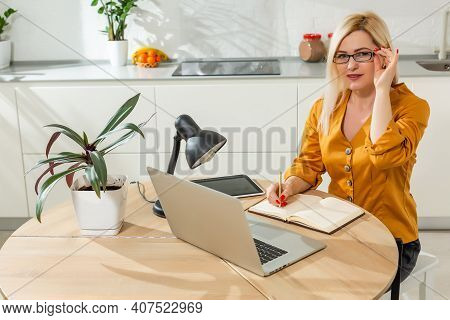 Remote Working From Home. Young Woman Using Laptop. Freelancer Workplace In Kitchen Office. Telework