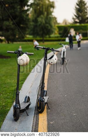 Two Electric Kick Scooters Or E-scooter Parked On The Sidelines Road