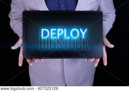 Deploy Word, Text Written In Neon Letters On A Laptop Which Is Being Held By A Businessman In A Gray