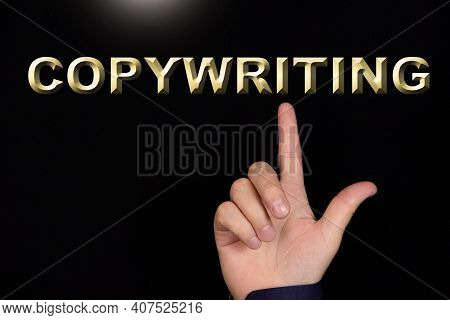 Copywriting Text, A Word Written On A Black Background Pointed To By A Hand With The Index Finger Of
