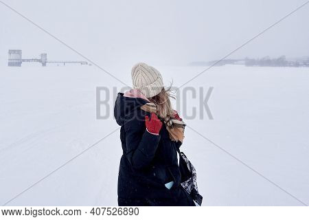 A Girl Walks Through A Snowstorm And Looks At An Old Abandoned Water Intake On A Frozen River.
