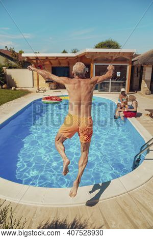 Group Of Elderly Friends Relaxing And Sunbathing By The Swimming Pool On A Hot Summer Day, One Man H