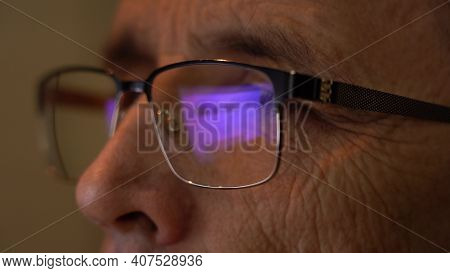 Senior Eyes With Glasses Close-up, Watching Content On The Internet. Reflection On Glasses From The
