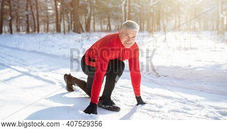 Outdoor Winter Activities. Mature Sportsman Getting Ready To Run Marathon On Snowy Road On Cold Sunn