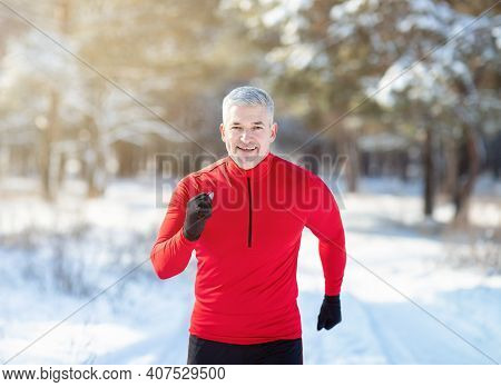 Cross Country Running In Winter. Happy Fit Senior Man Jogging In Snowy Forest On Sunny Morning. Spor