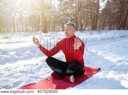 Outdoor Winter Yoga Concept. Peaceful Mature Man Sitting In Lotus Pose, Meditating With Closed Eyes