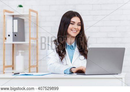 Online Visit To Therapist, Remote Consultation. Cheerful Young Cute Lady In White Coat Has Video Cal