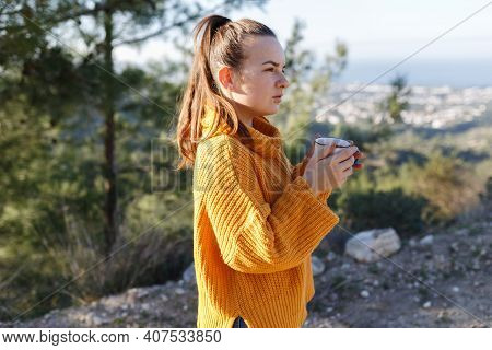 Woman Traveler In Autumn Mountains Above Sea. Cozy Fall Picnic With Coffee On Beach. Girl In Warm Pl