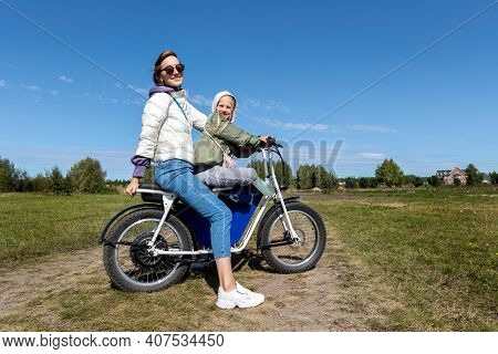 Young Adult Beautiful Mother And Daughter Enjoy Having Fun Riding Electric Scooter Bike Or Rural Cou