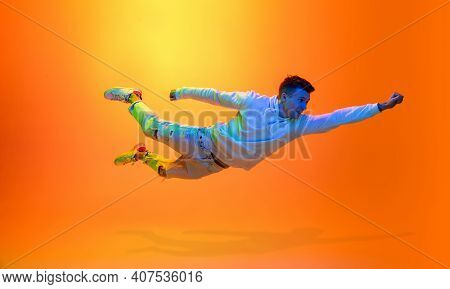 Flying Superhero. Caucasian Mans Portrait Isolated On Yellow Studio Background In Mixed Neon Light.