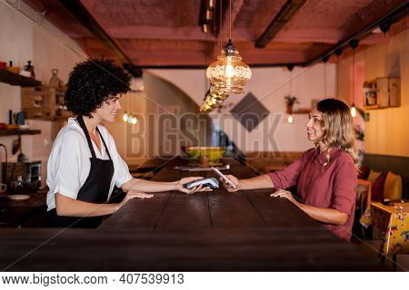 Smiling Woman Paying With Smart Phone Using Nfc Technology. Waitress Holding A Card Terminal Behind