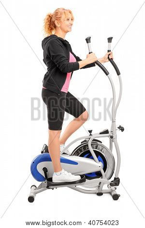 Full length portrait of a mature woman excersing on a cross trainer isolated on white background