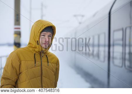Young Man Travel By Train During Frosty Day. Passenger On Platform Railroad Station In Winter Day.