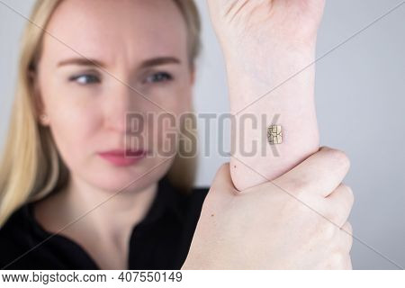 The Woman Shows His Hand With A Chip Implanted. The Concept Of Chipping And Implantation Of Electron