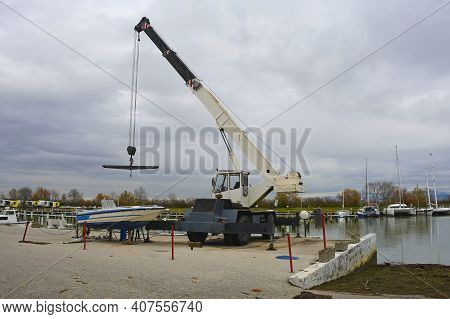 A Hydraulic Mobile Suspended Boat Lift Or Hoist With A Sling. Located In An Out-of-season Marina In