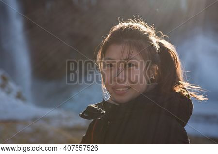 Hauyfoss Waterfall, Iceland - 03.11.2018: Travel Concept. Close Up Portrait Of A Happy Asian Woman W