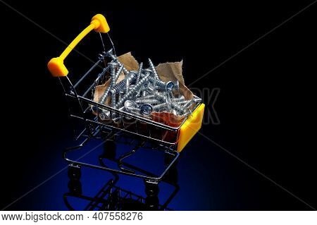 Steel Screws Lie On Craft Paper In A Small Shopping Cart. Advertising Photo For A Supplier Of Fasten