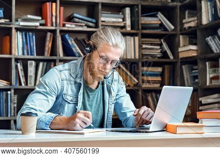 Focused Young Man Student Wear Headset Make Notes E Study Online In Library Listen Lecture Internet