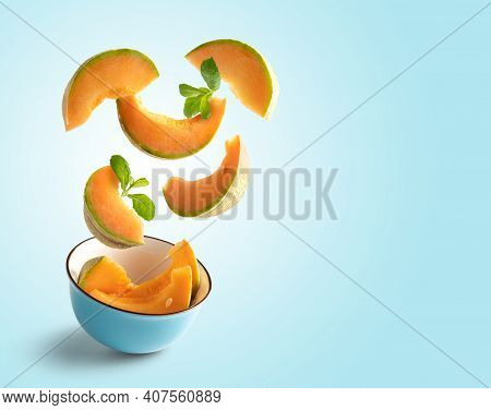 Cantaloupe Slices Flying On Blue Blue Background With Copy Space