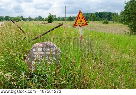 Warning Sign Radioactivity And Stone With Commemorative Inscription At Entrance To Resettled Village