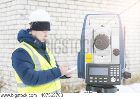 Engineer Surveyor Works With An Electronic Total Station, A Tool For Performing Geodetic, Constructi