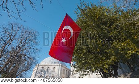 Turkish Flag On Background Of Mosque. Action. Turkish Flag Is Flying In Square Near Mosque. Travel A