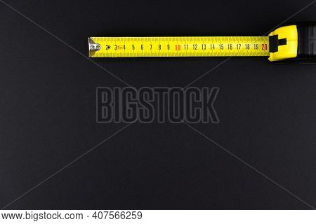 Measuring Tape Measure In Yellow On A Black Background