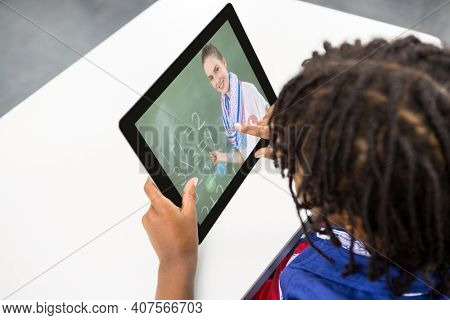 Mixed race schoolboy using digital tablet on video call with female teacher. Online education staying at home in self isolation during quarantine lockdown.