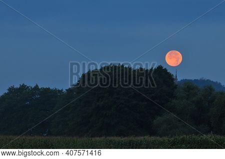 Full moon rising above a church\'s belfry