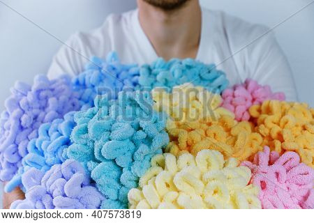 Man Holding Multi-colored Skeins Of Terry Yarn. Skeins Of Multicolored Terry Yarn Lined Up Like A Ra