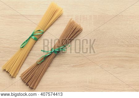 Two Bundles Of Dry Spaghetti Pasta On A Light Background With Copy Space