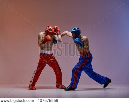 Athletic Guys Fighting, Wearing Boxing Gloves On Red Blue Studio Background With Copy Space, Mixed F