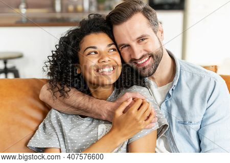 Hilarious Multiracial Couple In Love Sits In Embraces In Cozy Living Room At Home. A Close-up Portra