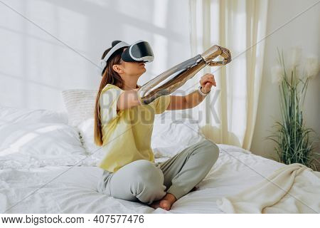 Young Woman With A Bionic Prosthetic Arm And Virtual Reality Glasses In A Yellow T-shirt And Gray Ho