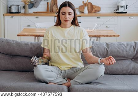 Woman With A Bionic Prosthetic Arm In A Yellow T-shirt Sits At Home On The Sofa In The Lotus Positio