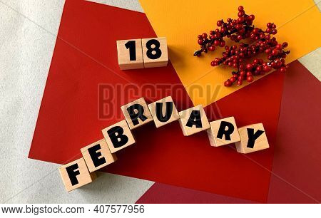 February 18 On A Multi-colored Background On Wooden Cubes.near Artificial Red Berries .winter.calend