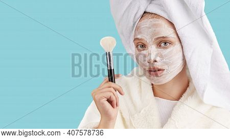 A young woman with a mask on her face, wearing a Bathrobe and a towel on her head, holding a makeup