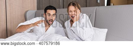 Excited Interracial Couple In Bathrobes Sitting On Bed In Hotel, Banner.