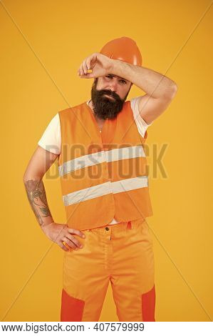 Working Hard. Tired Construction Worker Mop Sweat Yellow Background. Construction Engineer Or Builde