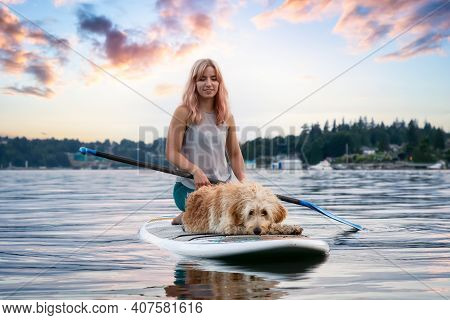 Girl With A Dog On A Paddle Board During A Vibrant Summer Sunset. Taken In Deep Cove, North Vancouve