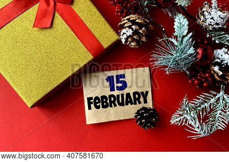 February 15 On Craft Paper. Near Fir Branches, Cones, Ribbon,gift Box On A Red Background.calendar F