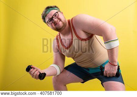 Fat Man Wearing Black Shirt Exercising With Dumbbells And Looking At Camera