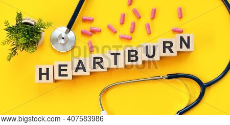 Heartburn Word Written On Wooden Blocks And Stethoscope, Pills, Green Potted Plant On Light Yellow T
