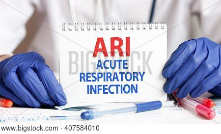Ari Card In Hands Of Medical Doctor. Doctor's Hands In Blue Gloves Holding A Sheet Of Paper With Tex