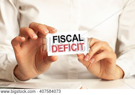 A Woman In A White Shirt Holds A Piece Of Paper With The Text: Fiscal Deficit. Business Concept For