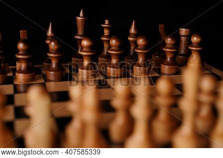 Close Up Of Black Chess Pieces On Board. Two Rows Of Wooden Figures On Chessboard On Black Backgroun