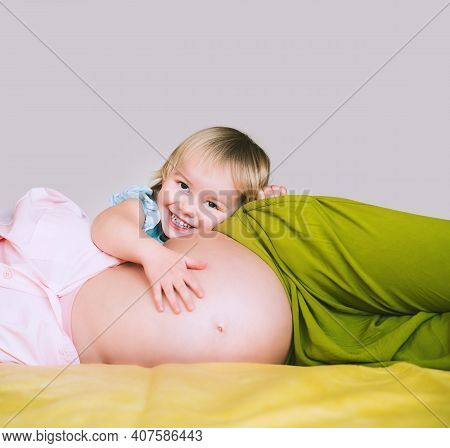 Pregnant Mother And Daughter Together At Home. Woman With Her First Child During Second Pregnancy. M