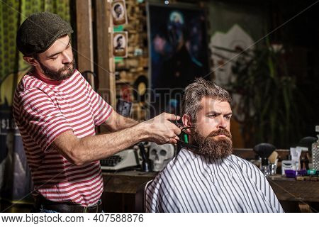 Bearded Man In Barbershop. Work In The Barber Shop. Hairdresser Cutting Hair Of Male Client. Hairsty