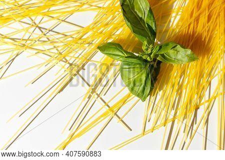 Dry Spaghetti Close-up And Fresh Green Basil Leaves. Hard Shadows, Selective Focus